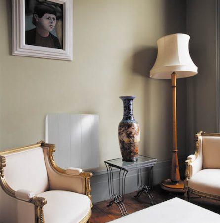 Needo, Gilt-framed French armchairs and tall vase on glass-topped metal table in living room with cream standard lamp